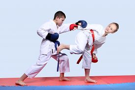 stock photo of karate-do  - On the red and blue mats athletes  are doing paired exercises karate - JPG