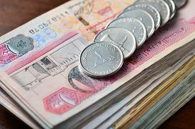 stock photo of dirham  - many one dirham coins placed on stack of hundred dirham notes - JPG