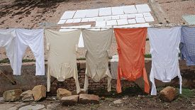 stock photo of gang  - Traditional clothing dried in the sun at Ganges riverbank Varanasi India - JPG