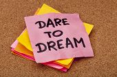 stock photo of daring  - dare to dream motivational slogan colorful sticky notes on cork bulletin board - JPG
