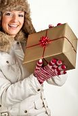 Caucasian blond woman in furry hat and christmas gifts isolated on white poster