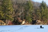 stock photo of bluegill  - a man ice fishing alone on a beautiful lake in early winter - JPG