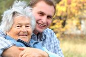 picture of young men  - an elderly person hugged by her grandson - JPG