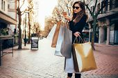 Woman Using A Smart Phone While Shopping In The City poster