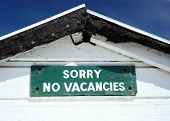 stock photo of saying sorry  - Traditional English beach hut with funny sign saying sorry no vacancies - JPG
