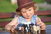 Cute Little Girl Playing With Farm Animal Toys Outdoors. poster