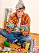 Repair home man holding paint bank. Tired and frustrated mad male in newspaper cap renovation apartm poster