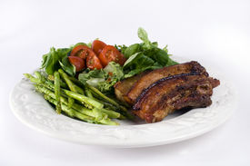 stock photo of pork belly  - A plate of food that consist of asparagus salad with tomato and belly pork isolated on a white background - JPG