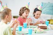 Group of hungry little kids eating glazed donuts with sprinkles poster