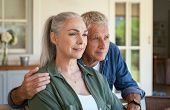 Old man embracing from behind his wife while sitting in front of house and contemplate future. Portr poster