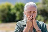 Senior woman having flu using nasal spray to help herself. Woman using a nasal spray at park for all poster