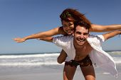 Front view of happy Mixed-race man giving piggyback to woman on beach in the sunshine poster