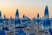 Blue Parasols And Sunbeds In Empty Rimini Resort Beach During The Evening Time And Illuminated By Or poster
