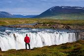 A tourist in a red jacket sightseeing. Waterfall Godafoss, Iceland. Amazing summer landscape with a  poster