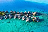 Travel vacation paradise aerial drone video with overwater bungalows in coral reef lagoon sea. Aeria poster