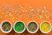 Sprinkles On Bright Orange Background With Little White Bowls With Various Type Of Coloured Sprinkle poster