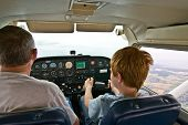 image of cessna  - joung boy is flying aircraft assisted by a trainer - JPG
