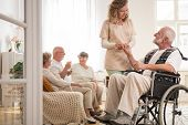 Senior Man On Wheelchair With Helpful Nurse Holding His Hand And Friends Sitting On Couch Drinking T poster