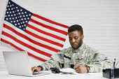Male Soldier Or Worker Of American Army Sitting At Table And Writing Documents, Using Laptop. Americ poster