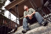 stock photo of social housing  - Middle aged man sitting on the steps of a house - JPG