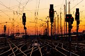 stock photo of traffic signal  - Railroad Tracks at a Major Train Station at Sunset.