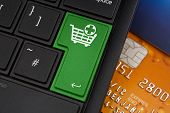 stock photo of qwerty  - Add to Cart Enter Key on a modern laptop qwerty keyboard with bank smart card underneath to represent online shopping - JPG