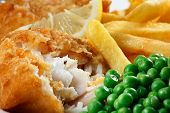 stock photo of pea  - Close up of fish and chips with peas and a slice of lemon. A traditional British Seaside Dish