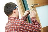 stock photo of handyman  - Male handyman carpenter at interior wood door lock installation - JPG