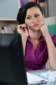 Wistful woman at a desk