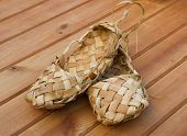stock photo of baste  - Russian bast shoes standing on the wooden floor - JPG