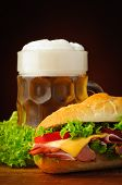 stock photo of deli  - still life with deli sub baguette sandwich and beer - JPG