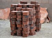 stock photo of xeriscape  - Stack of paving bricks, red charcoal color, with flagstones behind, ready for construction