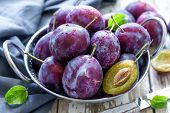 picture of plum fruit  - Fresh plums with leaves in a bowl