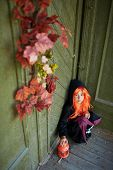 foto of antichrist  - Portrait of Halloween girl with red hair sitting on the porch of dilapidated house - JPG