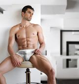 stock photo of abdominal muscle man  - Very sexy young fit man in white underwear in modern contemporary interior setting - JPG