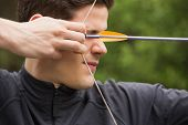 stock photo of archery  - Concentrated man practicing archery at the range - JPG
