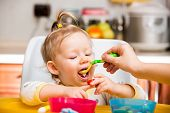 picture of porridge  - Child girl eats porridge from a spoon on kitchen - JPG