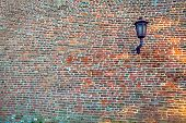 Lantern on a wall with bricks
