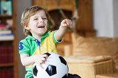 stock photo of carnival brazil  - Little blond preschool boy of 4 years with football watching soccer world cup on tv - JPG