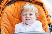 picture of christening  - Little baby boy in white christening gown clothes sitting in orange stroller