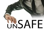pic of unsafe  - Businessman reaching his hand for the text Unsafe  - JPG