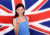 stock photo of united we stand  - Young woman standing with the UK flag in the background - JPG