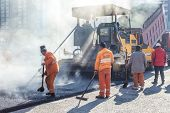 stock photo of paved road  - Workers making asphalt with shovels at road construction - JPG
