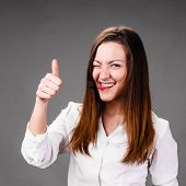 Portrait of winking and smiling business woman with thumbs up, on gray background