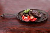 foto of peppercorns  - fresh roast beef fillet mignon on old retro style cast iron pan on retro wooden table as background with rosemary peppercorn and tomatoes - JPG