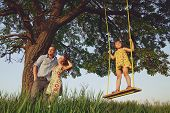picture of swings  - Beautiful girl on the swing in the forest with her parents - JPG
