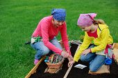 Gardening, sowing seeds to the soil -  girl helping mother in the garden
