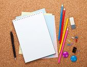 Blank notepad on cork wood notice board with office supplies