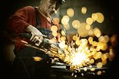 stock photo of labor  - Industrial worker cutting and welding metal with many sharp sparks - JPG