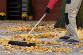image of dungarees  - A man sweeping leaves from his terrace - JPG